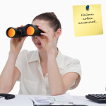 Young businesswoman looking through binoculars for new business